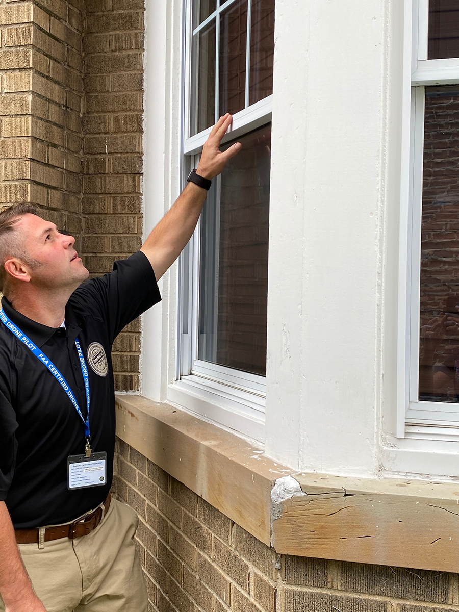 Matthew Chambers, one of our licensed home inspectors, inspecting the window outside of a house