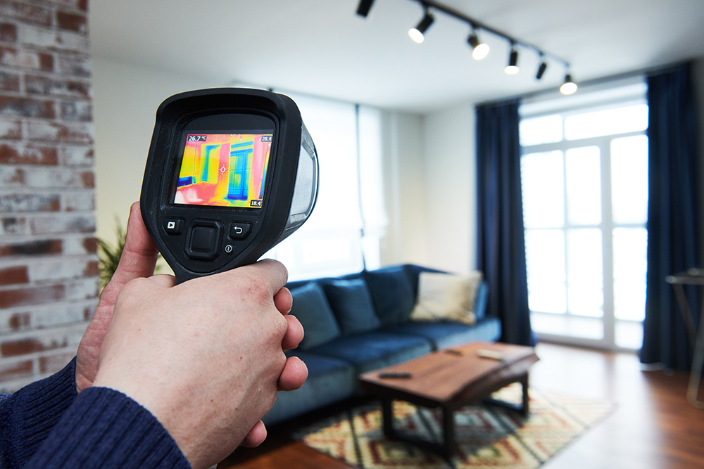 Thermal imaging camera being used in the living room of a house during home inspection services